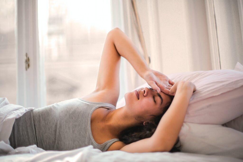 Woman having a headache in bed.